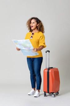 Giovane turista afroamericano stupito della donna con la mappa di mondo della tenuta della valigia