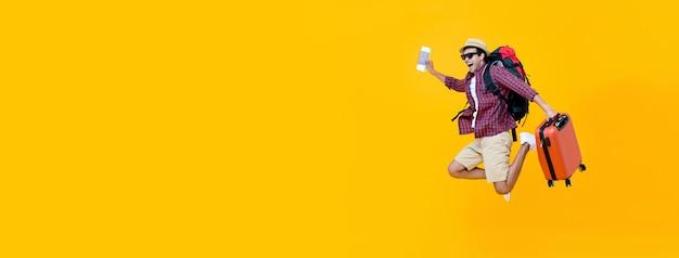 Giovane turista asiatico dell'uomo che salta con i bagagli