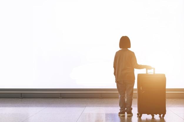 Giovane turista con bagagli che stanno davanti al grande tabellone per le affissioni della luce bianca all'aeroporto