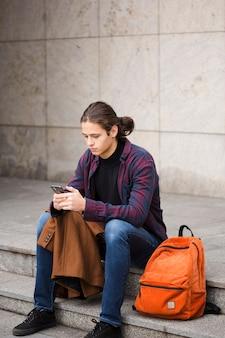 Giovane turista della foto a figura intera che controlla il suo telefono