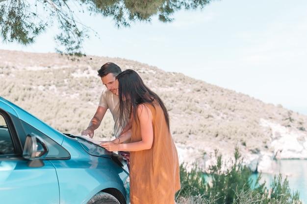 Giovane turista delle coppie con la mappa che viaggia in macchina