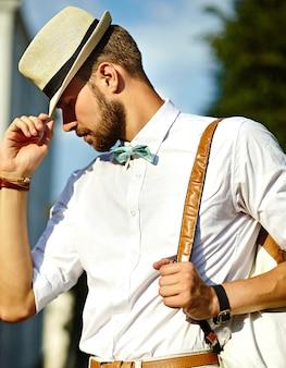 Giovane turista di modello bello sexy alla moda dell'uomo nello stile di vita casuale del panno nella via in cappello con la borsa