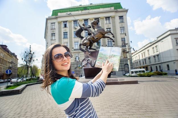 Giovane turista femminile con mappa alla ricerca sulla fotocamera e mostra la mappa