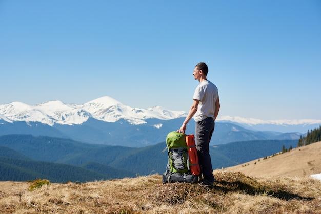 Giovane turista maschio che gode del sole di mattina in cima alla montagna dopo un'escursione