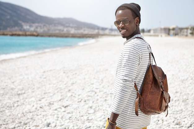 Giovane turista maschio dalla pelle scura bello allegro con lo zaino che cammina sulla spiaggia della ghiaia durante le vacanze al mare, vestita in vestiti alla moda