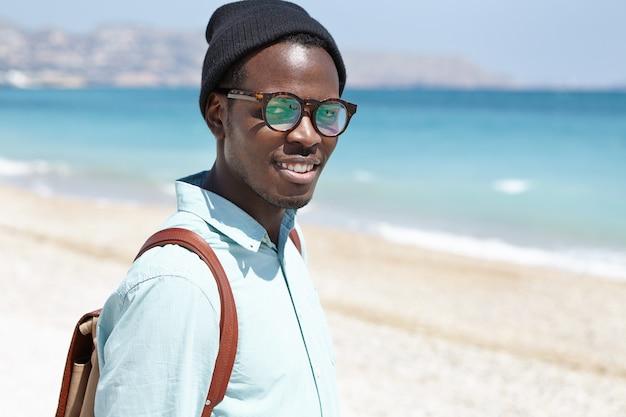 Giovane turista maschio europeo nero sembrante d'avanguardia moderno in occhiali e cappello che trasportano zaino che trascorrono giorno di molla soleggiato sulla spiaggia urbana, rallegrandosi al bel tempo e al mare calmo. viaggi e turismo