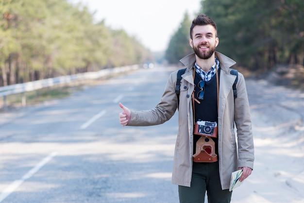 Giovane turista maschio sorridente con la macchina fotografica d'annata intorno al suo collo che fa auto autostop lungo una strada