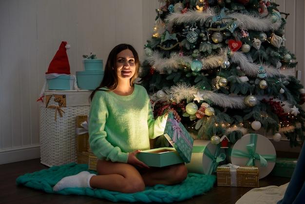 Giovane ubicazione felice della donna incinta vicino all'albero del nuovo anno e aprire un regalo.