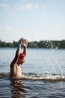 Giovane uomo a metà colpo nel lago