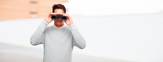 Giovane uomo abbronzato bello con il binocolo