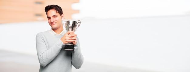 Giovane uomo abbronzato bello con un trofeo