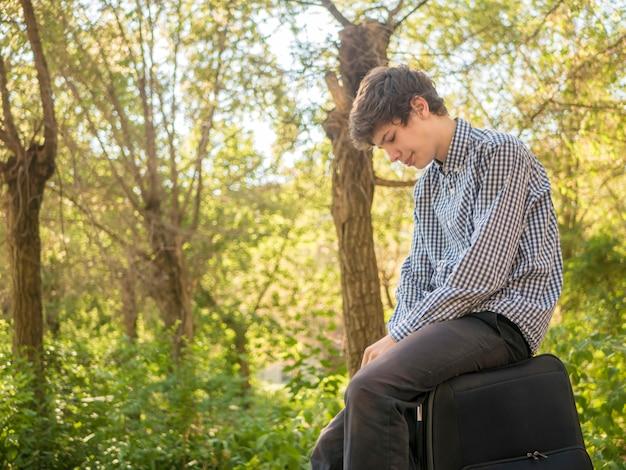 Giovane uomo adolescente stanco che si siede sulla grande borsa della borsa dei bagagli all'aperto nella via della città di estate