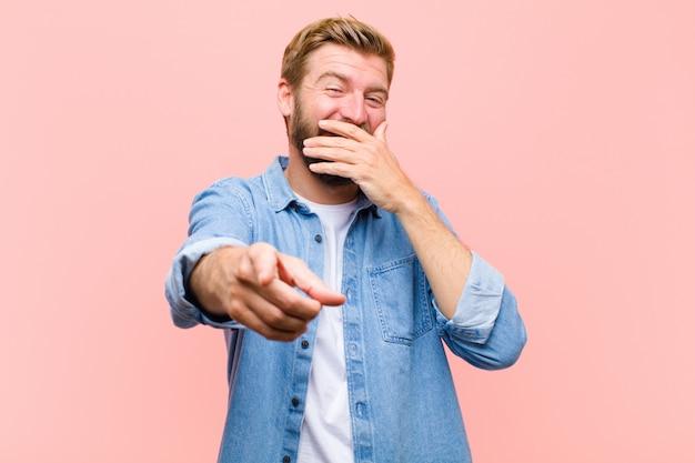 Giovane uomo adulto biondo che ride di te, indicando la macchina fotografica e prendendo in giro o prendendoti in giro