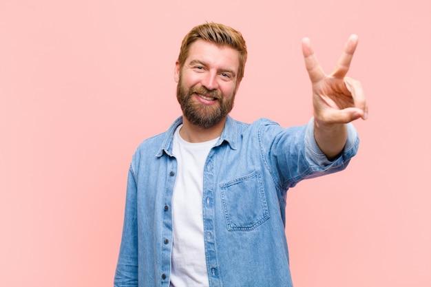 Giovane uomo adulto biondo che sorride e che sembra felice, spensierato e positivo, gesturing victorypeace con una mano
