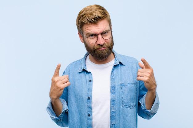 Giovane uomo adulto biondo con un cattivo atteggiamento che sembra orgoglioso e aggressivo, rivolto verso l'alto o prendendo in giro segno con le mani