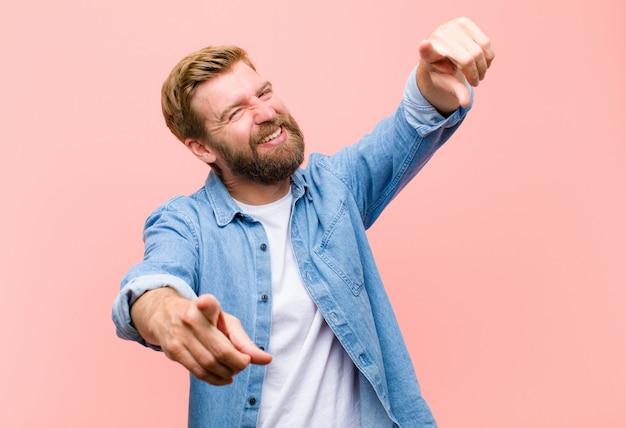 Giovane uomo adulto biondo sentirsi felice e fiducioso, indicando la fotocamera con entrambe le mani e ridendo, scegliendo te