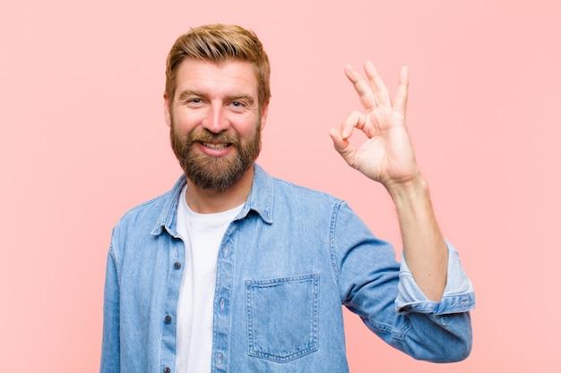 Giovane uomo adulto biondo sentirsi felice, rilassato e soddisfatto, mostrando approvazione con gesto ok, sorridendo