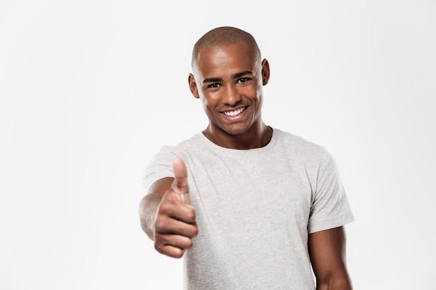 Giovane uomo africano allegro che mostra i pollici in su.