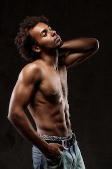 Giovane uomo africano allegro che posa sopra la parete nera.