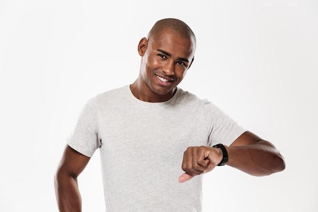 Giovane uomo africano allegro che usando orologio.