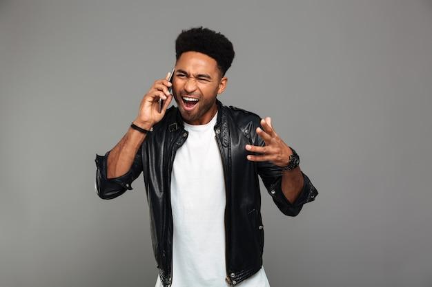 Giovane uomo africano arrabbiato che grida mentre parla sullo smartphone