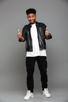 Giovane uomo africano attraente alla moda che mostra il pollice in alto gesto con due mani alla ricerca