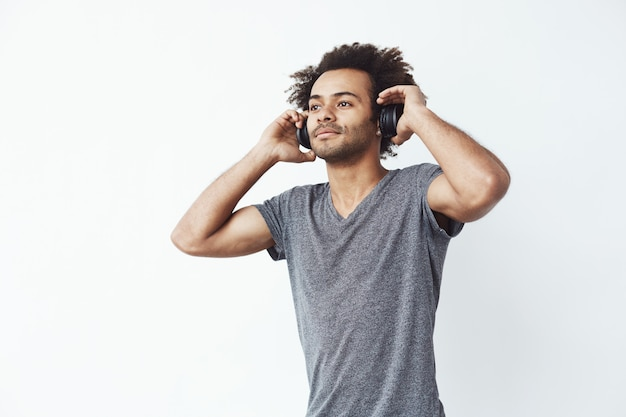 Giovane uomo africano bello che ascolta la musica in cuffie