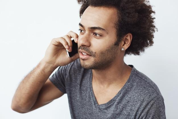 Giovane uomo africano bello che parla sul telefono.