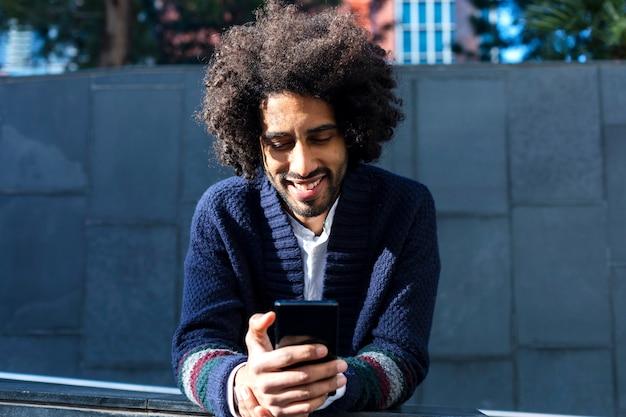 Giovane uomo africano bello che utilizza il suo smartphone con il sorriso mentre appoggiandosi un recinto all'aperto nel giorno soleggiato