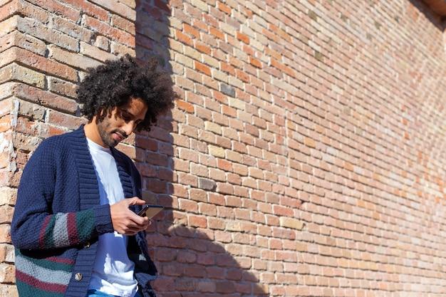 Giovane uomo africano bello che utilizza il suo smartphone con il sorriso mentre appoggiandosi una parete di mattoni all'aperto nel giorno soleggiato