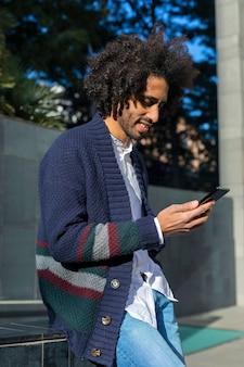 Giovane uomo africano bello che utilizza il suo smartphone con il sorriso mentre sedendosi su un banco all'aperto nel giorno soleggiato