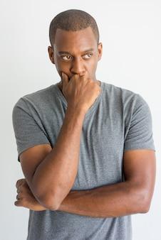 Giovane uomo africano bello pensieroso che si appoggia a disposizione mentre pensando.