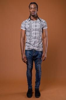Giovane uomo africano bello su sfondo marrone