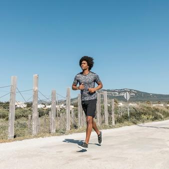 Giovane uomo africano che corre lungo la strada