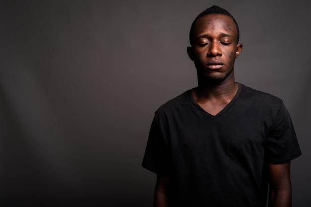 Giovane uomo africano che porta camicia nera sulla parete grigia