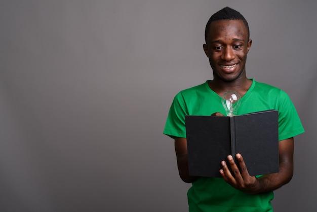 Giovane uomo africano che porta camicia verde sulla parete grigia