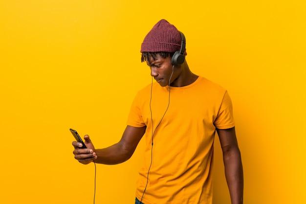 Giovane uomo africano che sta contro una parete gialla che porta un cappello che ascolta la musica con un telefono