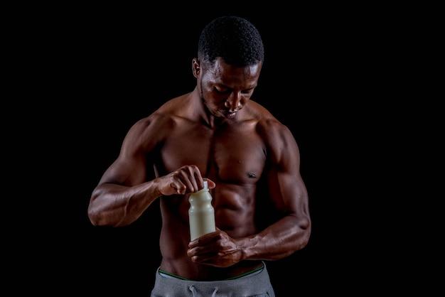 Giovane uomo africano in buona salute che esercita tenendo latte. allenamento bodybuilder