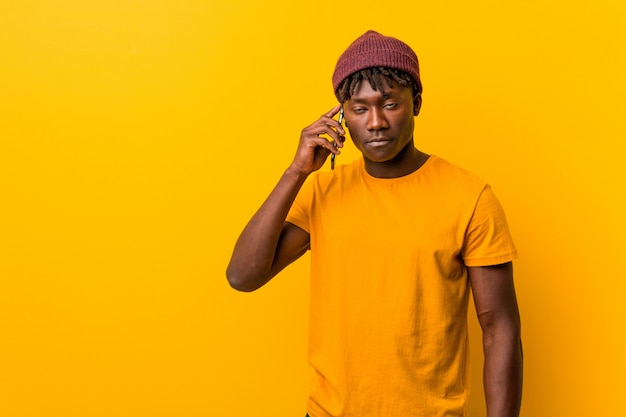 Giovane uomo africano in piedi su uno sfondo giallo che indossa un cappello e utilizzando un telefono