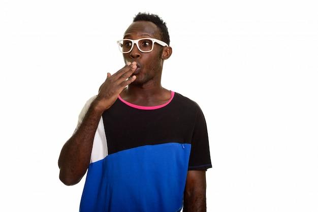 Giovane uomo africano nero che sembra colpito mentre coprendo bocca