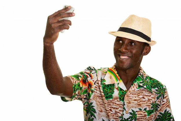 Giovane uomo africano nero felice che sorride e che prende selfie con il cellulare