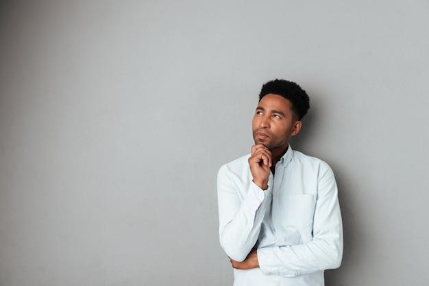 Giovane uomo africano pensieroso che osserva via lo spazio della copia