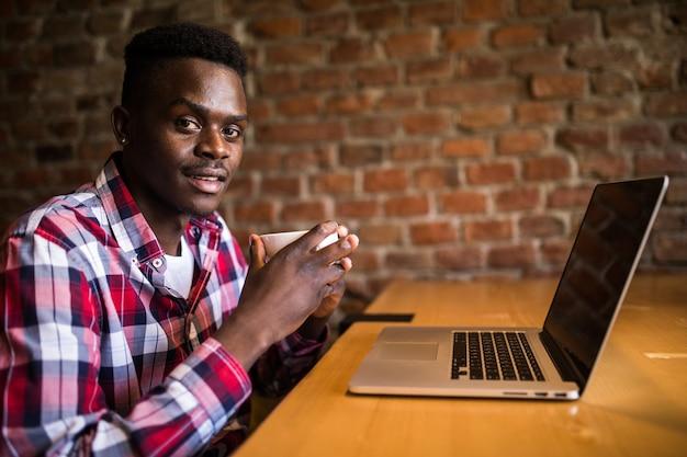 Giovane uomo africano seduto presso la caffetteria con il computer portatile. studente che indossa abiti alla moda, beve caffè, utilizza internet wireless. concetto di tecnologia e comunicazione