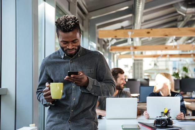 Giovane uomo africano sorridente che sta nell'ufficio che chiacchiera dal telefono