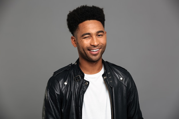 Giovane uomo africano sorridente in giacca di pelle nera strizza l'occhio, guardando
