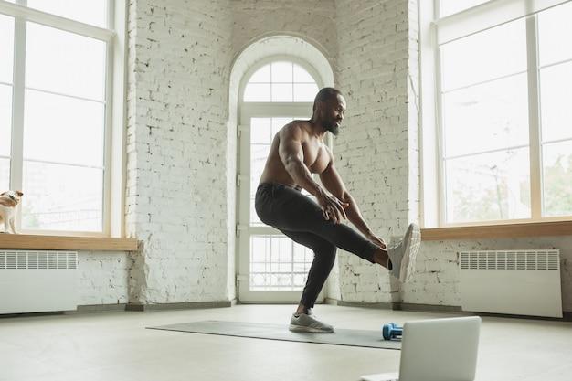 Giovane uomo afro-americano allenamento a casa, facendo esercizi di fitness, aerobica.