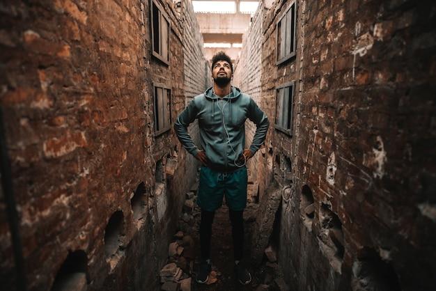 Giovane uomo afro sportivo che sta fra due mura di mattoni e cercare. vecchio interno di fabbrica di mattoni.