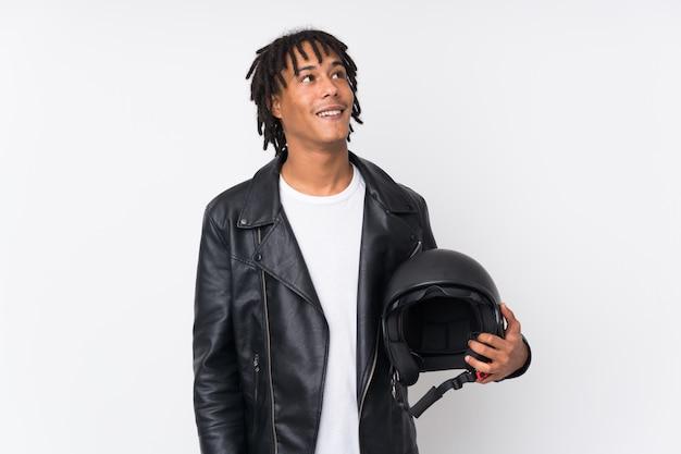 Giovane uomo afroamericano che giudica un casco del motociclo isolato sulla parete bianca che cerca mentre sorridendo