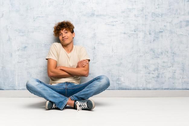Giovane uomo afroamericano che si siede sul pavimento che fa il gesto di dubbi mentre sollevando le spalle