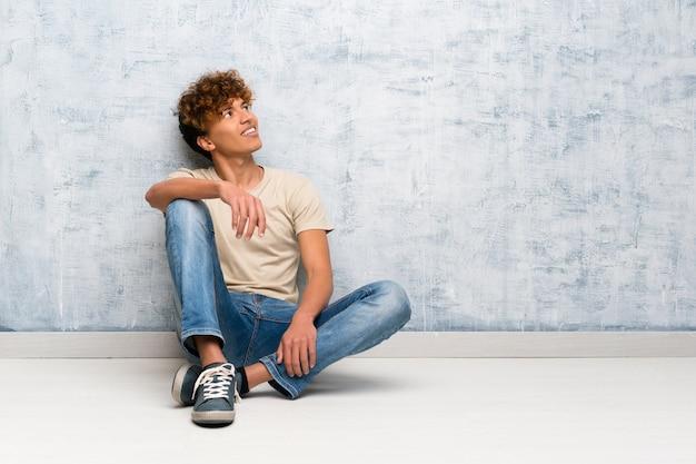 Giovane uomo afroamericano che si siede sul pavimento felice e sorridente